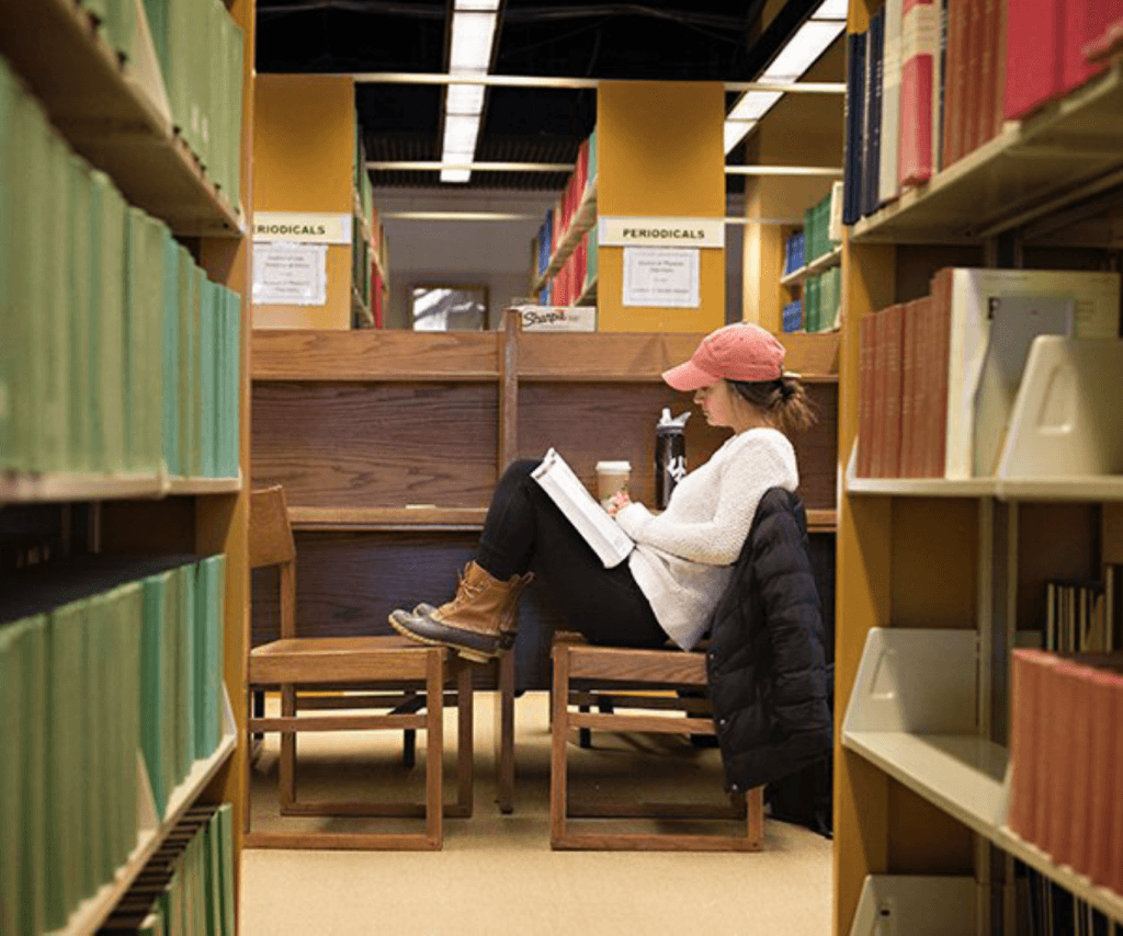 Student reading at a carrel in the stacks