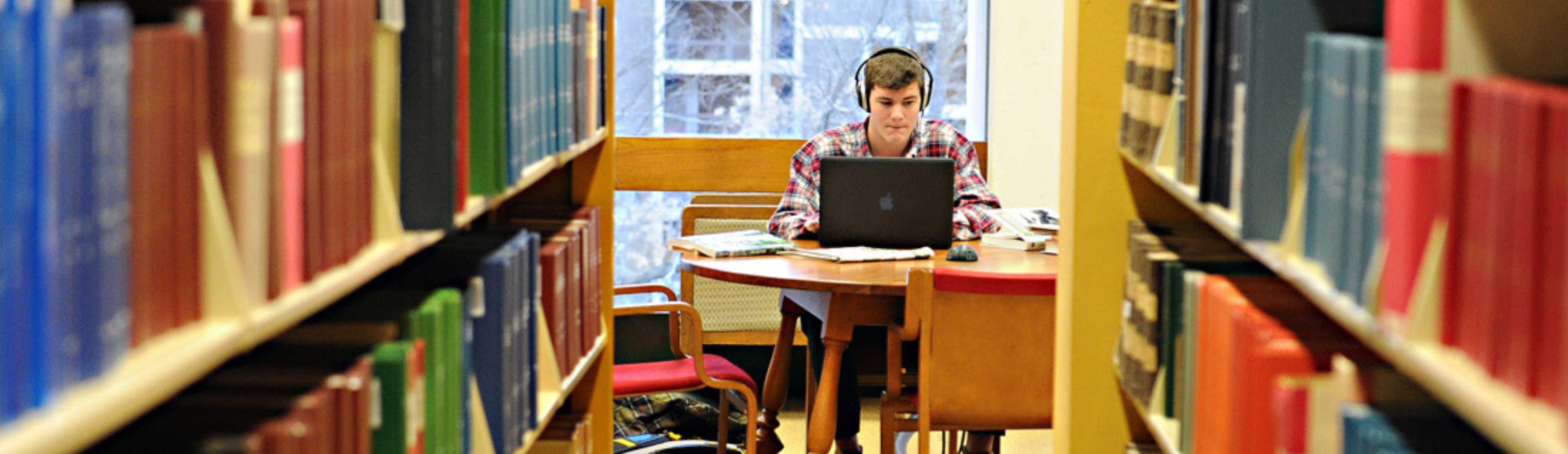 Student studying in the stacks
